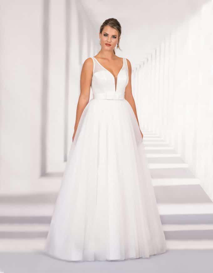 Langes Brautkleid mit tiefem Ausschnitt und großer Schleife